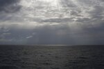 In this photo taken on Sunday, Sept. 8, 2019, the sun pierces the clouds over international waters north of Libya in the Mediterranean Sea. The humanitarian rescue ship operated by SOS Mediterranee and Doctors Without Borders, has requested Italian and Maltese authorities for the medical evacuation of a pregnant woman and a place of safety for the other 83 rescued migrants. (AP Photo/Renata Brito)