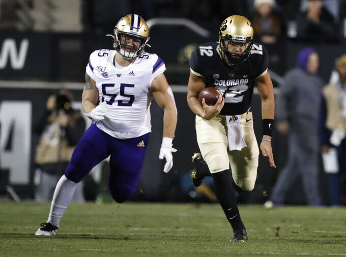 Colorado quarterback Steven Montez runs for a short gain as Washington linebacker Ryan Bowman pursues during the first half of an NCAA college football game Saturday, Nov. 23, 2019, in Boulder, Colo. (AP Photo/David Zalubowski)