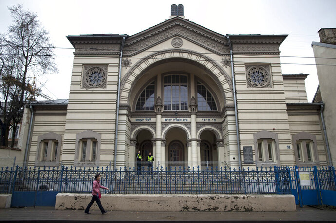"""In this photo taken on Wednesday, Oct. 31, 2018, a woman walks past a synagogue in Vilnius, Lithuania. Jewish leaders in the Lithuanian capital are closing the city's sole synagogue and community center indefinitely following a string of threats sparked by an emotional debate over history. Community leader Faina Kukliansky told The Associated Press on Wednesday, Aug. 7, 2019 that """"our community is receiving threatening calls and letters lately. (AP Photo/Mindaugas Kulbis)"""