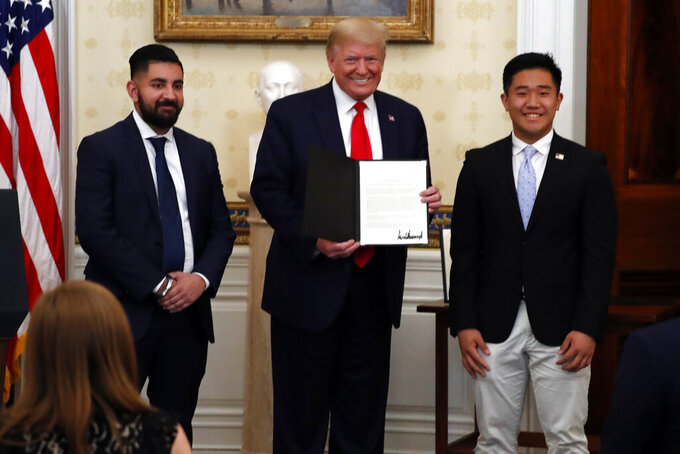 """FILE - President Donald Trump poses for a photo with TJ Kim, a sophomore at The Landon School, and Bobby Chahal, who flies TJ in his plane, during an event to honor volunteers helping to battle the coronavirus, in the Blue Room of the White House, Friday, May 1, 2020, in Washington. For more than a year, The Associated Press has been bringing you """"One Good Thing"""" — stories highlighting good deeds done by individuals to brighten others' days during trying times.  (AP Photo/Alex Brandon, File)"""