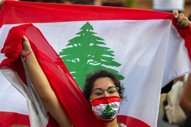 An anti-government protester shouts slogans while wearing a mask with the colors of the Lebanese flag in Beirut, Lebanon, Thursday, July 2, 2020. Major retailers in Lebanon announced Thursday they will temporarily close in the face of an increasingly volatile currency market and their inability to set prices while the local currency tumbles before the dollar. (AP Photo/Hassan Ammar)
