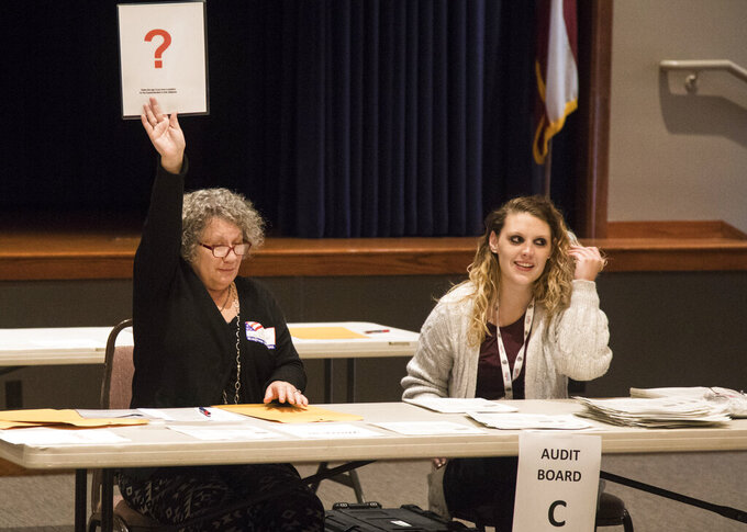 Walker County election officials Joy Chrnalogar and Krista Richardson raise a sign to indicate a ballot in need of review during the first day of recounts for the 2020 election at the Walker County Civic Center on Friday, Nov. 13, 2020, in Rock Spring, Ga. (Troy Stolt/Chattanooga Times Free Press via AP)