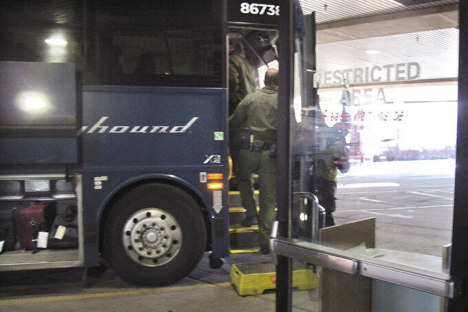 FILE - In this Thursday, Feb. 13, 2020 file photo, agents for Customs and Border Protection board a Greyhound bus headed for Portland, Ore., at the Spokane Intermodal Center, a terminal for buses and Amtrak, in Spokane, Wash. Greyhound Lines Inc. will pay $2.2 million to settle a lawsuit over the bus line's practice of allowing U.S. Customs & Border Protection agents to board its buses in Washington state to conduct warrantless immigration sweeps, the state attorney general said Monday, Sept. 27, 2021. (AP Photo/Nicholas K. Geranios, File)