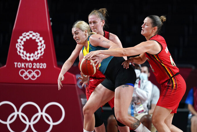 Australia's Cayla George, center, drives between Belgium's Emma Meesseman and Jana Raman, right, during a women's basketball preliminary round game at the 2020 Summer Olympics, Tuesday, July 27, 2021, in Saitama, Japan. (AP Photo/Charlie Neibergall)