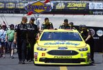 The crew of Paul Menard pushes his car through the pits after practice for a  NASCAR Cup series auto race, Friday, April 13, 2018, in Bristol, Tenn. (AP Photo/Wade Payne)