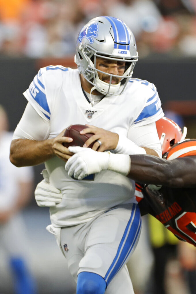 Detroit Lions quarterback Tom Savage, left, is sacked during the first half of the team's NFL preseason football game against the Cleveland Browns, Thursday, Aug. 29, 2019, in Cleveland. (AP Photo/Ron Schwane)