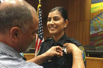 This Aug. 2, 2018 photo provided by Williams Pioneer Review shows Merced Corona, left, pins his daughter Natalie Corona's badge on her uniform during a swearing-in ceremony in Davis, Calif. Natalie Corona was shot and killed during a routine call Thursday, Jan. 10, 2019. (Williams Pioneer Review via AP)