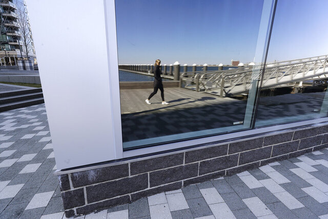 A woman is reflected in a window of a building along the waterfront in the Seaport District of Boston, Thursday, March 26, 2020. Many people are working from home while many businesses have closed indefinitely because of the coronavirus, leaving portions of the city nearly empty. The new coronavirus causes mild or moderate symptoms for most people, but for some, especially older adults and people with existing health problems, it can cause more severe illness or death. (AP Photo/Steven Senne)