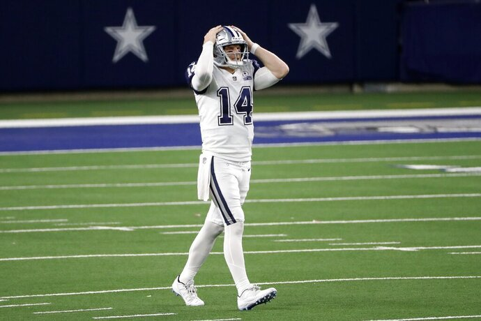 Dallas Cowboys quarterback Andy Dalton (14) grabs his helmet after throwing an incomplete pass into the end zone in the second half of an NFL football game against the Washington Football Team in Arlington, Texas, Thursday, Nov. 26, 2020. (AP Photo/Roger Steinman)