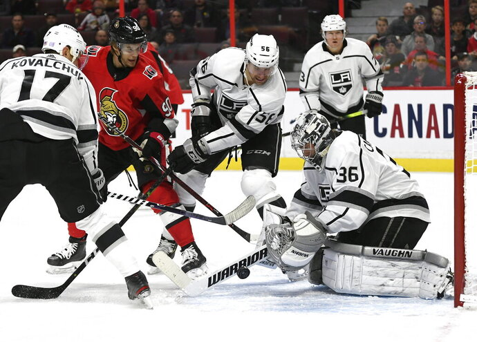 Los Angeles Kings goaltender Jack Campbell (36) reaches for the puck as defenseman Kurtis MacDermid (56) and left wing Ilya Kovalchuk (17) defend against Ottawa Senators center Vladislav Namestnikov (90) during second-period NHL hockey game action in Ottawa, Ontario, Thursday, Nov. 7, 2019. (Justin Tang/The Canadian Press via AP)