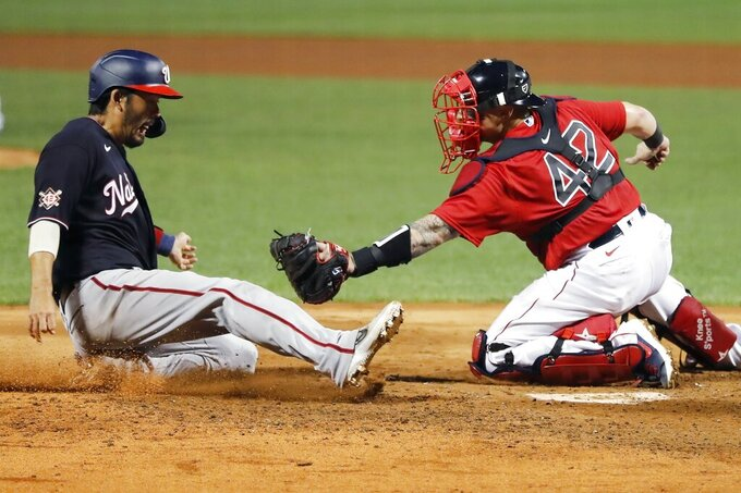 Boston Red Sox's Christian Vazquez, right, tags out Washington Nationals' Kurt Suzuki at home plate during the fifth inning of a baseball game, Saturday, Aug. 29, 2020, in Boston. (AP Photo/Michael Dwyer)