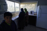 The wife, daughter and son of Abdul (not shown), who worked as a mechanic before he left Kabul, Afghanistan with his family about a month ago, stand, Thursday, Sept. 16, 2021, in the kitchen of the rental house the family has been provided as a place to stay in Seattle. The home is owned by Thuy Do, who was nine years old when her family arrived in the United States from Vietnam in the 1980s. Now Do and her husband have offered their vacant rental home to refugee resettlement groups to house newly arriving Afghans in need of a place to stay. (AP Photo/Ted S. Warren)
