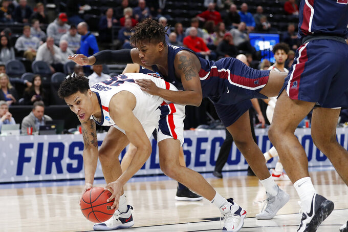 Gonzaga forward Brandon Clarke, left, takes a hit by Fairleigh Dickinson forward Elyjah Williams, right, in the first half during a first round men's college basketball game in the NCAA Tournament, Thursday, March 21, 2019, in Salt Lake City. (AP Photo/Jeff Swinger)