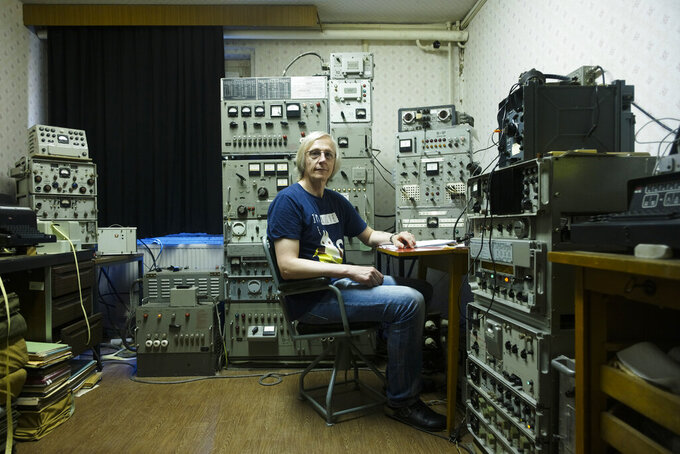 Jens Raeder sits between carefully restored Soviet shortwave transmitter he use for communication with military radio enthusiasts around the world in the village Harnekop at a rural region east of Berlin, Germany, Wednesday, Aug. 12, 2020. With the next generation of mobile technology, known as 5G, people in rural areas hope for a better internet connection than with the current 4G system. (AP Photo/Markus Schreiber)