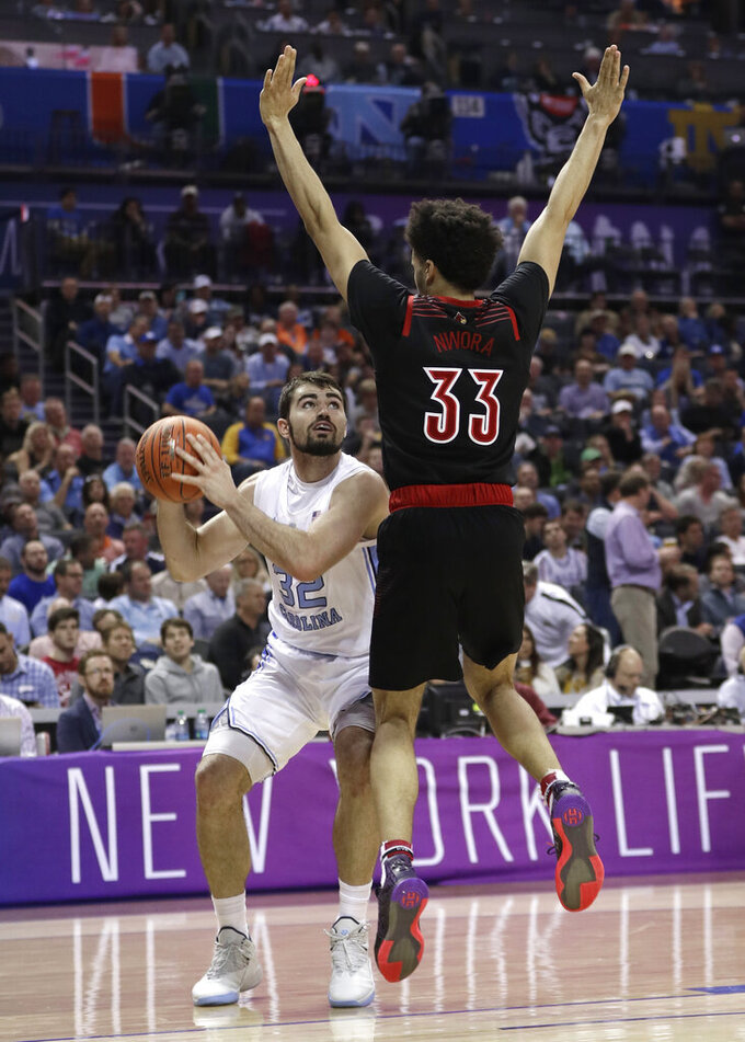 North Carolina's Luke Maye (32) tries to shoot over Louisville's Jordan Nwora (33) during the second half of an NCAA college basketball game in the Atlantic Coast Conference tournament in Charlotte, N.C., Thursday, March 14, 2019. (AP Photo/Nell Redmond)
