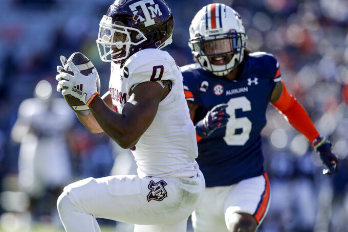 Texas A&M running back Ainias Smith (0) catches a pass over Auburn defensive back Christian Tutt (6) during the second half of an NCAA college football game on Saturday, Dec. 5, 2020, in Auburn, Ala.  (AP Photo/Butch Dill)