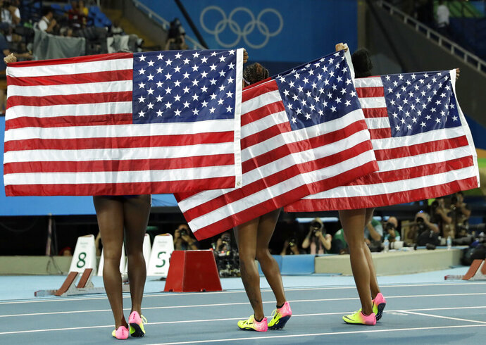 """FILE - In this Aug. 17, 2016, file photo, gold medal winner Brianna Rollins, center, silver medal winner Nia Ali, left, and bronze medal winner Kristi Castlin, all from the United States, pose with their country's flag after the 100-meter hurdles final during the athletics competitions of the 2016 Summer Olympics at the Olympic stadium in Rio de Janeiro, Brazil. If the Tokyo Olympics were opening today - actually they begin exactly a year from now - the United States would top the overall medal count, and the gold-medal count. That's the forecast released Tuesday, July 22, 2019, by Gracenote Sports, which bills itself as a """"sports and entertainment provider"""" and supplies statistical analysis for sports league around the world. (AP Photo/Matt Dunham, File)"""