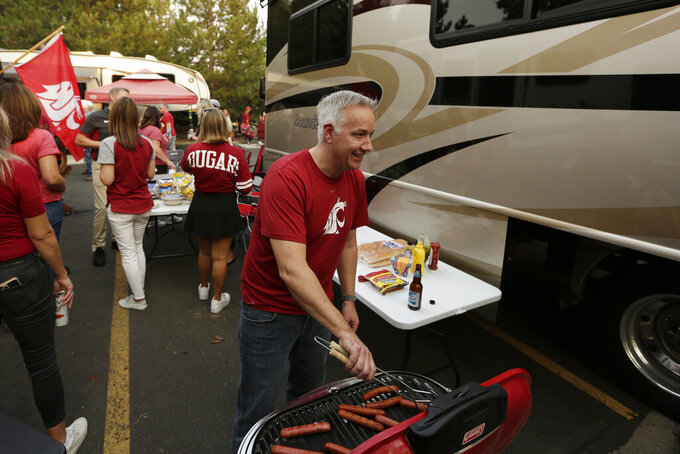 Michael Braunz grills hot dogs before an NCAA college football game between Washington State and Utah State, Saturday, Sept. 4, 2021, in Pullman, Wash. (AP Photo/Young Kwak)