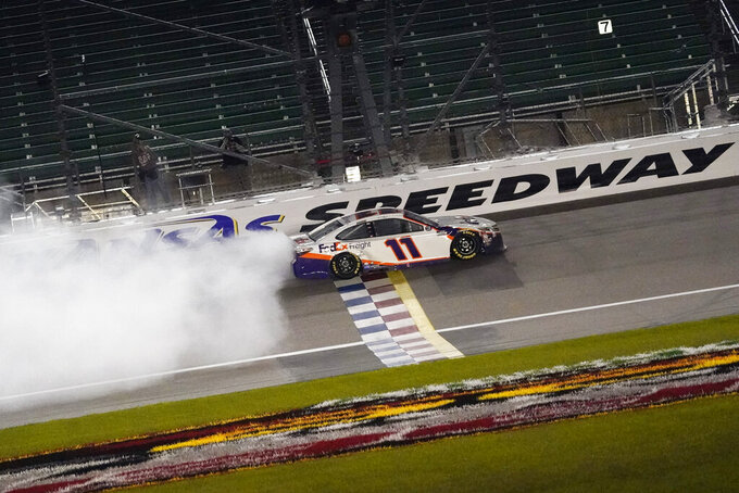 Denny Hamlin does a burnout after winning a NASCAR Cup Series auto race at Kansas Speedway in Kansas City, Kan., Thursday, July 23, 2020. (AP Photo/Charlie Riedel)