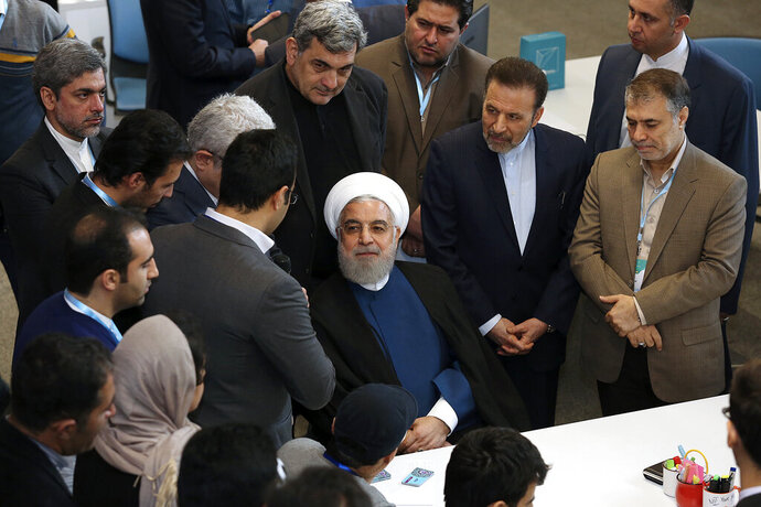 In this photo released by the official website of the office of the Iranian Presidency, President Hassan Rouhani, center, attends a ceremony to inaugurate Azadi Innovation Factory in Pardis technology park in west of Tehran, Iran, Tuesday, Nov. 5, 2019. Rouhani announced on Tuesday that Tehran will begin injecting uranium gas into 1,044 centrifuges, the latest step away from its nuclear deal with world powers since President Donald Trump withdrew from the accord over a year ago. (Office of the Iranian Presidency via AP)