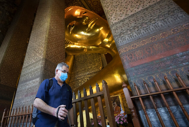 In this Friday, March 13, 2020, photo, a tourist wearing protective mask walk in front of giant Buddha at Wat Pho temple in Bangkok, Thailand. Wat Pho, which is one of Thailand's major tourist attractions and famous for housing the golden 46-meter- (151-foot-) long Reclining Buddha, has barred entry to foreigners, professing fear that they could spread COVID-19. (AP Photo/Sakchai Lalit)