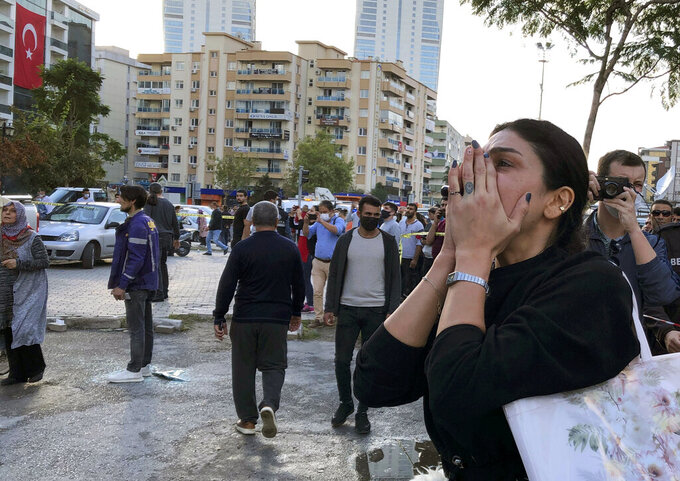 A woman watches as rescue workers try to save people trapped in the debris of a collapsed building, in Izmir, Turkey, Friday, Oct. 30, 2020. A strong earthquake struck Friday in the Aegean Sea between the Turkish coast and the Greek island of Samos, killing several people and injuring hundreds amid collapsed buildings and flooding, officials said.(AP Photo/Ismail Gokmen)
