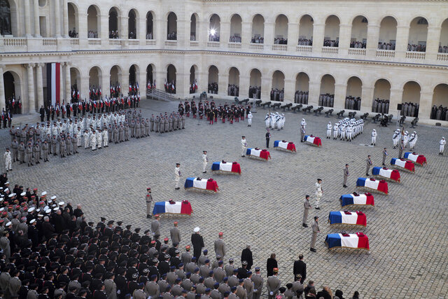 Coffins of 13 French soldiers killed in Mali lay at the Invalides monument during a ceremony Monday Dec.2, 2019 in Paris. In its biggest military funeral in decades, France is honoring 13 soldiers killed when their helicopters collided over Mali while on a mission fighting extremists affiliated with the Islamic State group. (AP Photo/Rafael Yaghobzadeh)