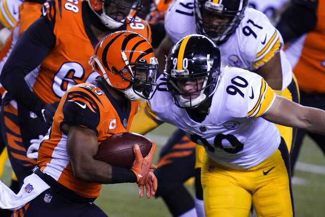 Cincinnati Bengals' Giovani Bernard (25) is tackled by Pittsburgh Steelers outside linebacker T.J. Watt (90) during the first half of an NFL football game, Monday, Dec. 21, 2020, in Cincinnati. (AP Photo/Michael Conroy)