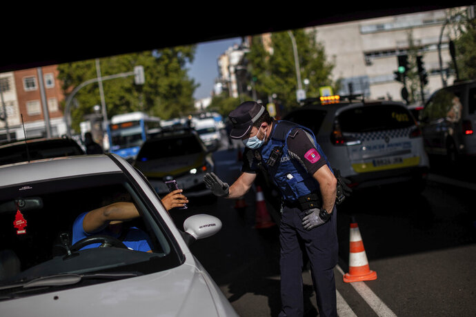 A local police stops a vehicle at a checkpoint in Madrid, Spain, Monday, Sept. 21, 2020. Police in the Spanish capital and its surrounding towns are stopping people coming in and out of working-class neighborhoods that have been partially locked down to stem Europe's fastest coronavirus spread. (AP Photo/Bernat Armangue)