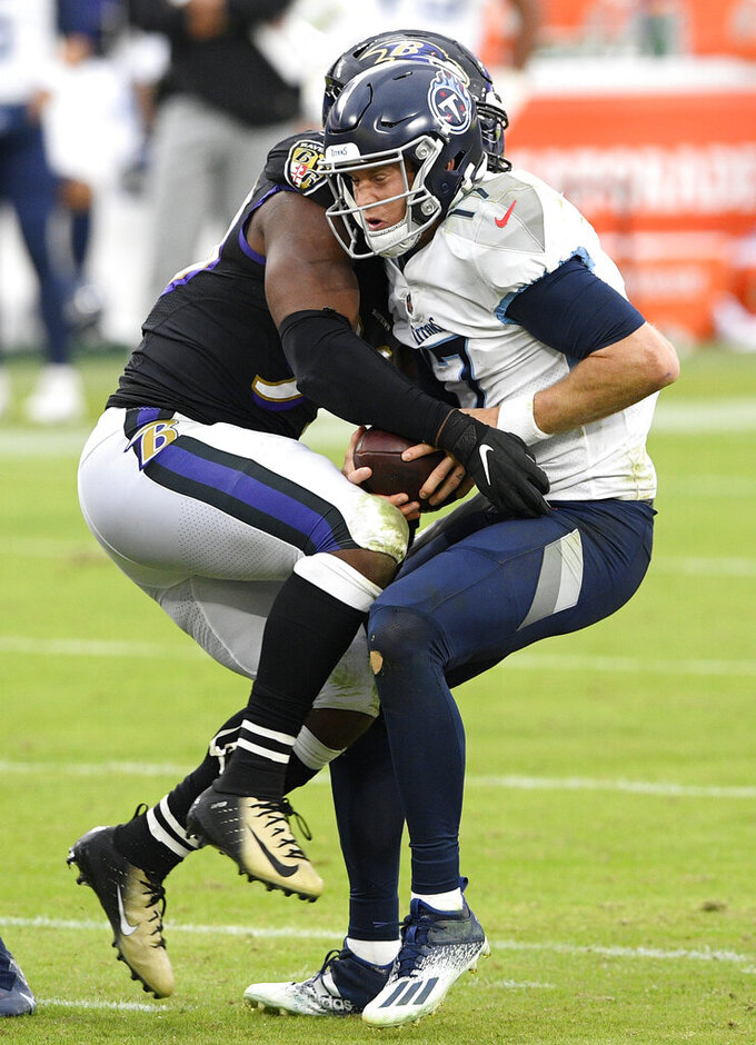 Tennessee Titans quarterback Ryan Tannehill, right, is sacked by Baltimore Ravens outside linebacker Matt Judon during the second half of an NFL football game, Sunday, Nov. 22, 2020, in Baltimore. (AP Photo/Nick Wass)