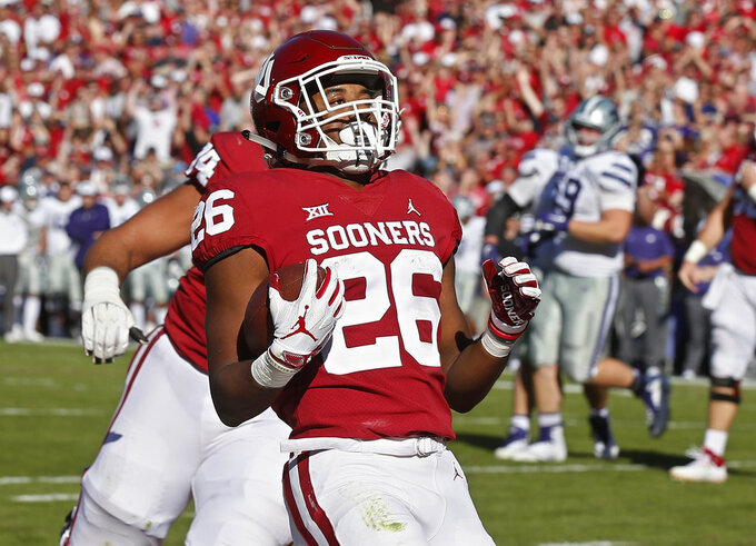Oklahoma running back Kennedy Brooks (26) scores in front of teammate Cody Ford, left, in the first half of an NCAA college football game against Kansas State in Norman, Okla., Saturday, Oct. 27, 2018. (AP Photo/Sue Ogrocki)