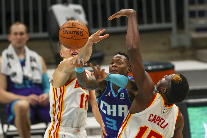 Charlotte Hornets guard Terry Rozier, center, passes between Atlanta Hawks guard Bogdan Bogdanovic, left, and center Clint Capela, right, during the second quarter of an NBA basketball game in Charlotte, N.C., Sunday, April 11, 2021. (AP Photo/Nell Redmond)
