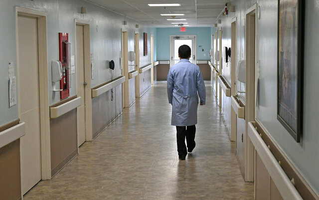 James Lin, D.O., walks down a hallway at the LECOM Nursing and Rehabilitation Center in Erie, Pa., on Monday, March 30, 2020. The staff at the facility have prepared this wing of the facility for possible future LECOM patients, including those who have tested positive for COVID-19, and those who need to be tested. (Christopher Millette/Erie Times-News via AP)
