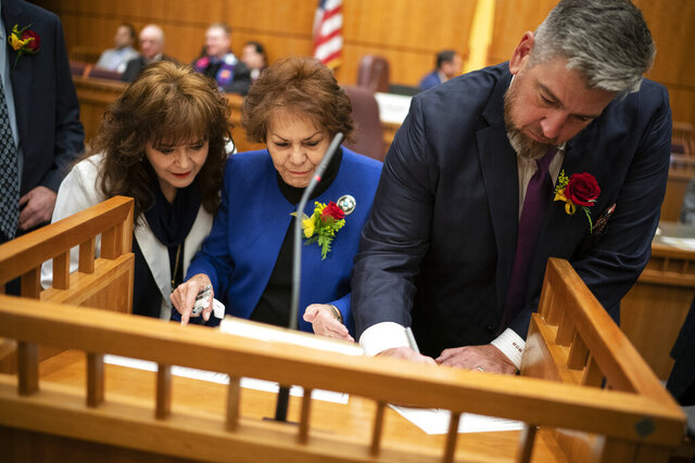 Chief Clerk of the Senate Lenore Naranjo, center, helps state Sens. Nancy Rodriguez and Mark Moores sign the roll at the beginning of the New Mexico legislative session in Santa Fe, N.M. on Tuesday, Jan. 21, 2020. (AP Photo/Craig Fritz)