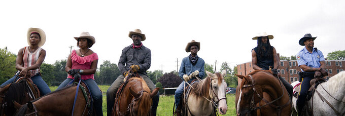 """This image released by Netflix shows, from left, Ivannah-Mercedes, Lorraine Toussaint, Idris Elba, Caleb McLaughlin, Jamil """"Mil"""" Prattis and Cliff """"Method Man"""" Smith in a scene from """"Concrete Cowboys."""" (Jessica Kourkounis/Netflix via AP)"""