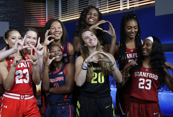 Utah's Daneesha Provo, far left, and teammate Megan Huff, second from left, pose with Arizona players Sam Thomas, third from top left, and Aarion McDonald, below Thomas, along with Oregon's Ruthy Hebard, top, and Sabrina Ionescu, bottom, and Stanford's Dijonai Carrington, top, and Kiana Williams, bottom,  during NCAA college basketball Pac-12 women's media day in San Francisco, Wednesday, Oct. 10, 2018. (AP Photo/Jeff Chiu)