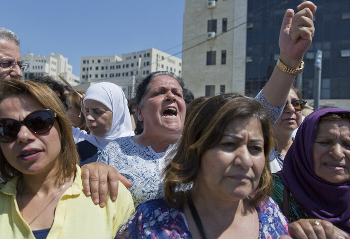 FILE - In this Monday, Sept. 2. 2019 file photo, a Palestinian woman chants slogans during a rally in front of the Prime Minister's office, in the West Bank city of Ramallah. On Thursday, Sept. 12, 2019, Palestinian Attorney General Akram al-Khatib said that three people, all relatives, are being charged in the death of  Israa Ghrayeb, a 21-year-old woman, in a suspected honor killing. Protesters demanding justice in the case said they were satisfied with the charges. (AP Photo/Nasser Nasser, File)