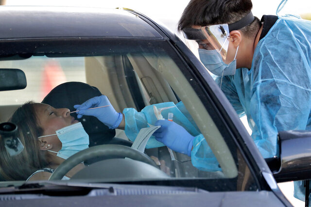 FILE - In this June 27, 2020, file photo, people are tested in their in vehicles in Phoenix's western neighborhood of Maryvale with free COVID-19 tests. Arizona Gov. Doug Ducey has ordered the state's hospitals, testing labs and other health care facilities to keep reporting detailed COVID-19 information. The move was made so state officials can gauge the spread of the outbreak and availability of hospital beds and resources. Ducey on Wednesday, Nov. 12, 2020, extended the reporting requirement for 60 days. (AP Photo/Matt York, File)