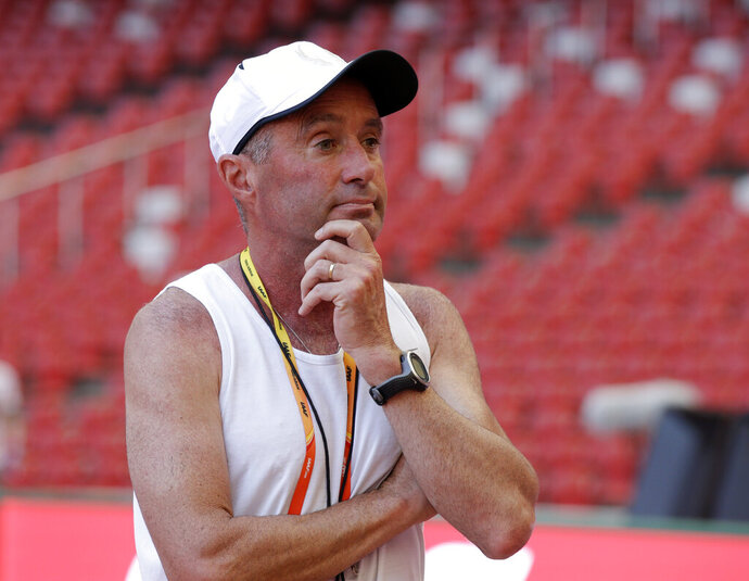 FILE - In this Aug. 21, 2015, file photo, track coach Alberto Salazar watches a training session for the upcoming World Athletic Championships at the Bird's Nest stadium in Beijing. Salazar, who trained four-time Olympic champion Mo Farah and a number of other top runners, has been given a four-year ban by the U.S. Anti-Doping Agency. USADA said in a news release Monday, Sept. 30, 2019, that Salazar and Jeffrey Brown were receiving four-year bans for, among other violations, possessing and trafficking testosterone while working at the Nike Oregon Project (NOP), where they trained top runners. (AP Photo/Kin Cheung, File)
