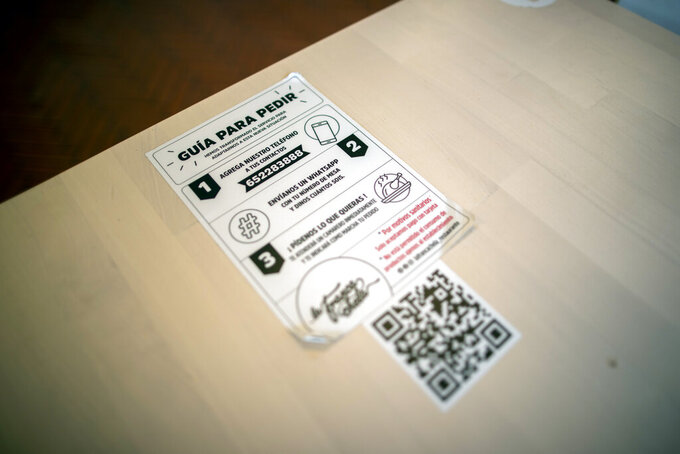 A sticker with the instructions to order is pictured at La Francachela restaurant in Madrid, Spain, Friday, March 26, 2021. Experimenting with cutting back one workday per week is about to go nationwide in Spain. A 3-year pilot project will be using 50 million euros ($59 million) from the European Union's massive coronavirus recovery fund to compensate companies as they resize their workforce or reorganize production workflows to adapt to a 32-hour working week. (AP Photo/Manu Fernandez)