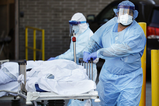 Medical workers wearing personal protective equipment wheel bodies to a refrigerated trailer serving as a makeshift morgue at Wyckoff Heights Medical Center, Monday, April 6, 2020, in the Brooklyn borough of New York. The new coronavirus causes mild or moderate symptoms for most people, but for some, especially older adults and people with existing health problems, it can cause more severe illness or death. (AP Photo/John Minchillo)