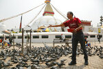 In this May 9, 2019 photo, Apa Sherpa feeds pigeons in Boudhanath Stupa in Kathmandu, Nepal. Apa Sherpa has stood on top of the world more times than all but one other person. Now he wants to make sure no one feels compelled to follow in his footsteps. (AP Photo/Niranjan Shrestha)