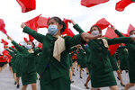 Women wearing face masks to help curb the spread of the coronavirus parade with flags during a rally to welcome the 8th Congress of the Workers' Party of Korea at Kim Il Sung Square in Pyongyang, North Korea, Monday, Oct. 12, 2020. (AP Photo/Jon Chol Jin)