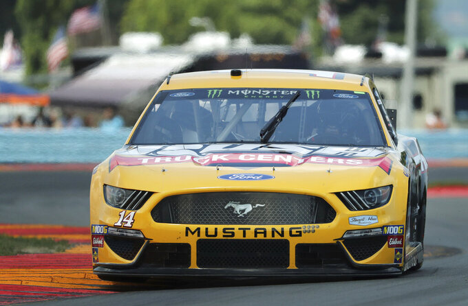 "Clint Bowyer (14) heads through the area known as ""The Bus Stop"" during a practice run for a NASCAR Cup Series auto race at Watkins Glen International, Saturday, Aug. 3, 2019, in Watkins Glen, N.Y. (AP Photo/John Munson)"
