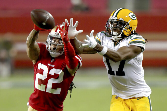 FILE - San Francisco 49ers cornerback Jason Verrett (22) intercepts a pass in front of Green Bay Packers wide receiver Davante Adams (17) during an NFL football game in Santa Clara, Calif., in this Thursday, Nov. 5, 2020, file photo. The 49ers are bringing back cornerback Jason Verrett on a one-year deal. General manager John Lynch announced the deal on Monday, March 15, 2021, shortly after Verrett was allowed to begin talking to other teams about a potential deal. NFL Network reported the contract has a $5.5 million base value with the chance to make more. (AP Photo/Scot Tucker, File)