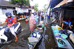People make their way through flood water in Banjarmasin, South Kalimantan on Borneo Island, Indonesia, Sunday, Jan. 17, 2021.  many thousands of people have been evacuated and a number have been killed in recent days in flooding on Indonesia's Borneo island, officials said Sunday. (AP Photo/Iman Satria)