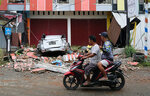 Motorist ride past the wreckage of a car damaged in an earthquake in Mamuju, West Sulawesi, Indonesia, Friday, Jan. 15, 2021. A strong, shallow earthquake shook Indonesia's Sulawesi island just after midnight, causing landslides and sending people fleeing from their homes in the nighttime darkness. (AP Photo/Sadly Ashari Said)