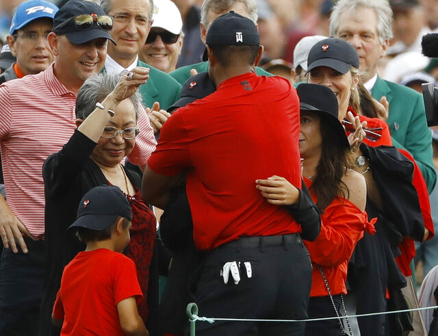 FILE - In this April 14, 2019 file photo, Tiger Woods hugs his family after winning the Masters golf tournament in Augusta, Ga. His reaction when he won, with his children there, stood out among the other 14 majors Woods has won. (AP Photo/Matt Slocum, File)