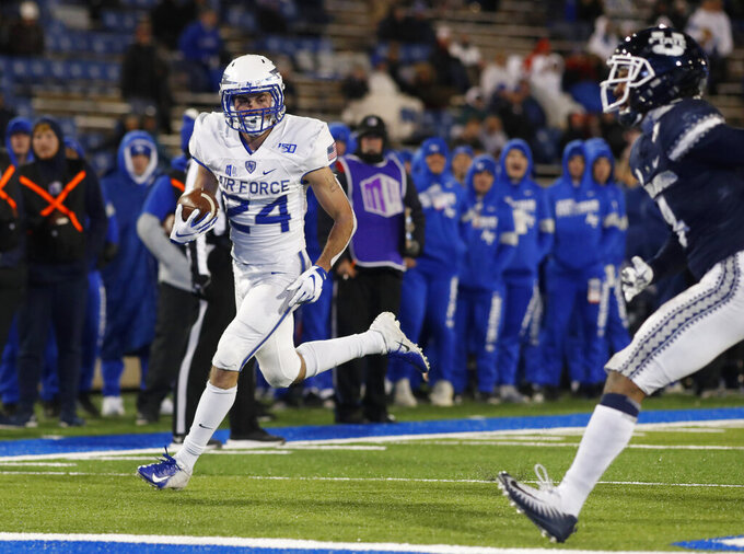 Air Force running back Kadin Remsberg, left, outruns Utah State safety Shaq Bond to score a touchdown in the second half of an NCAA college football game Saturday, Oct. 26, 2019, at Air Force Academy, Colo. Air Force won 31-7. (AP Photo/David Zalubowski)