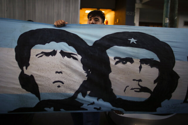 A soccer fan stands behind a banner featuring former soccer star Diego Maradona and Marxist revolutionary Ernesto